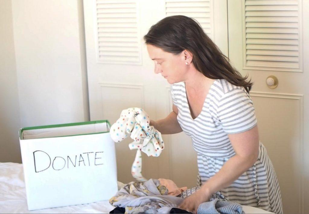 women putting green shirt in donation box