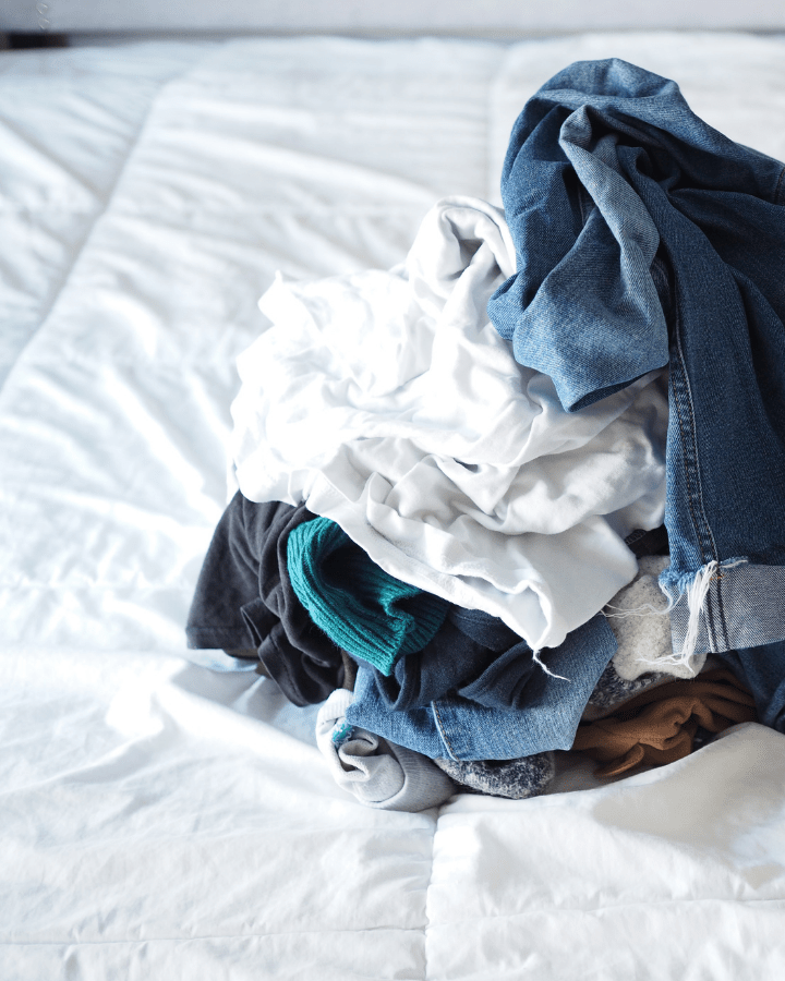 pile of laundry on a white bed