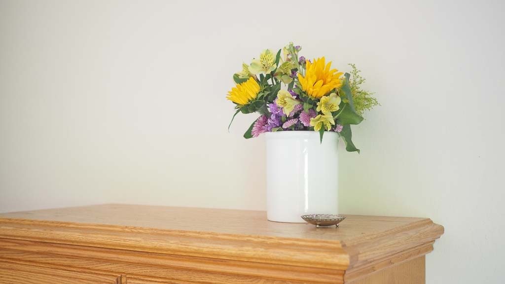 flowers on to of a dresser for the bedroom cleaning checklist