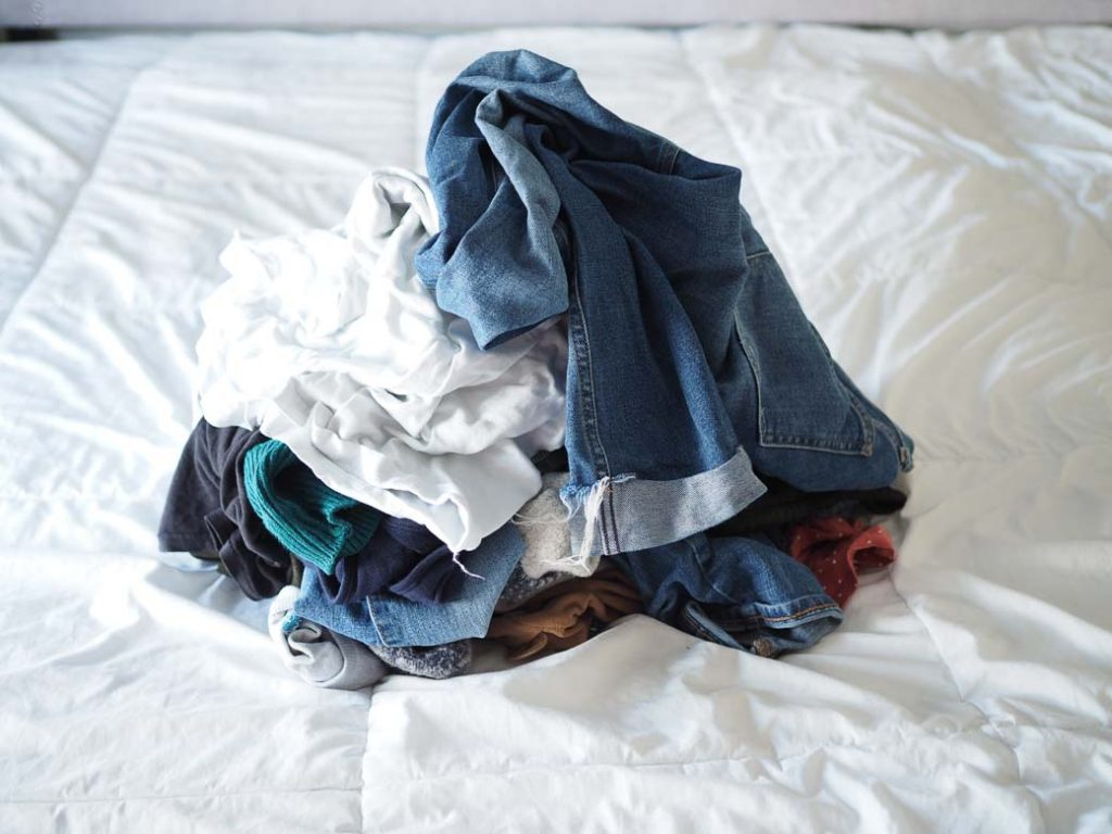 pile of clean clothes on a white bed
