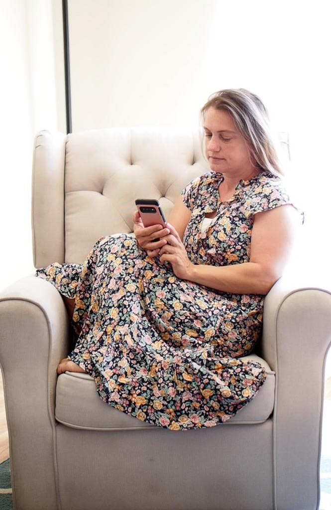 woman sitting on a chair and looking at phone