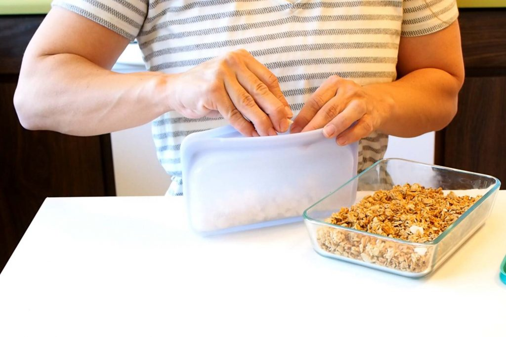women placing a snack in a stasher sandwich bag for another eco-friendly swaps in the kitchen
