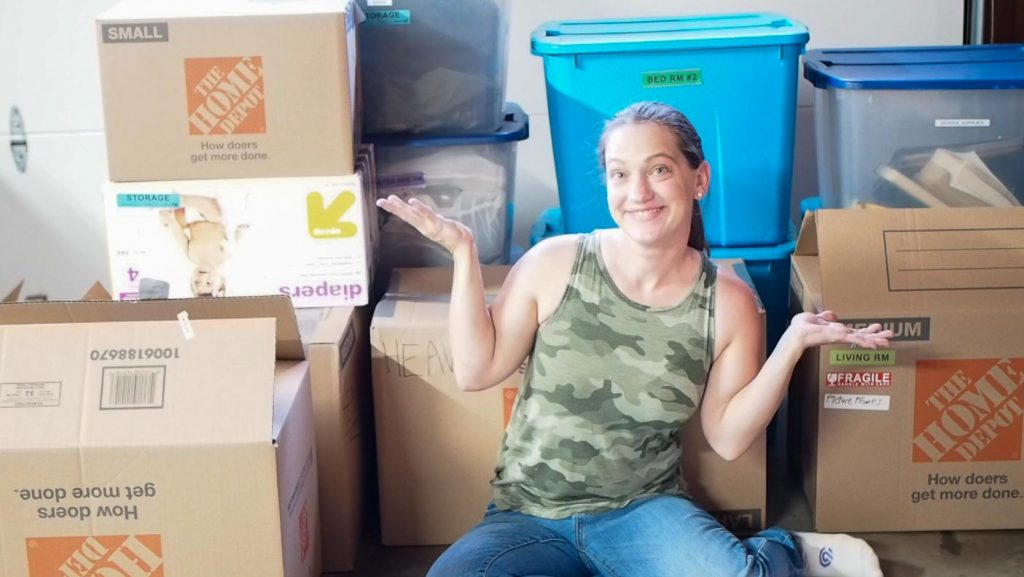 women siting in front of packed moving boxes