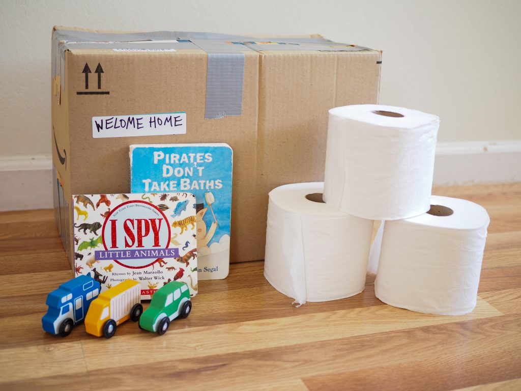 brown moving box packed with toilet paper and essentials for the family is another moving tips & tricks when you have children