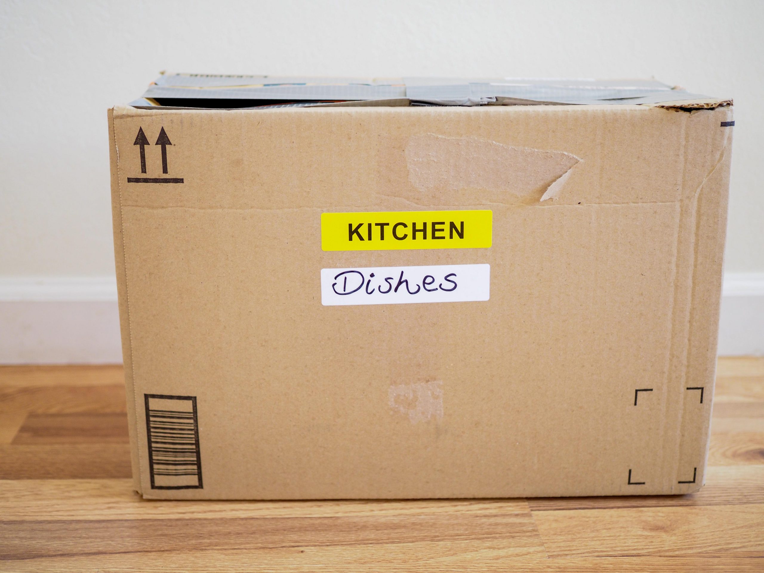 brown moving box with the label kitchen and dishes written on it