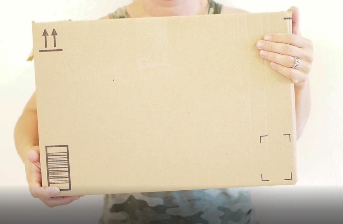 women holding a brown moving box