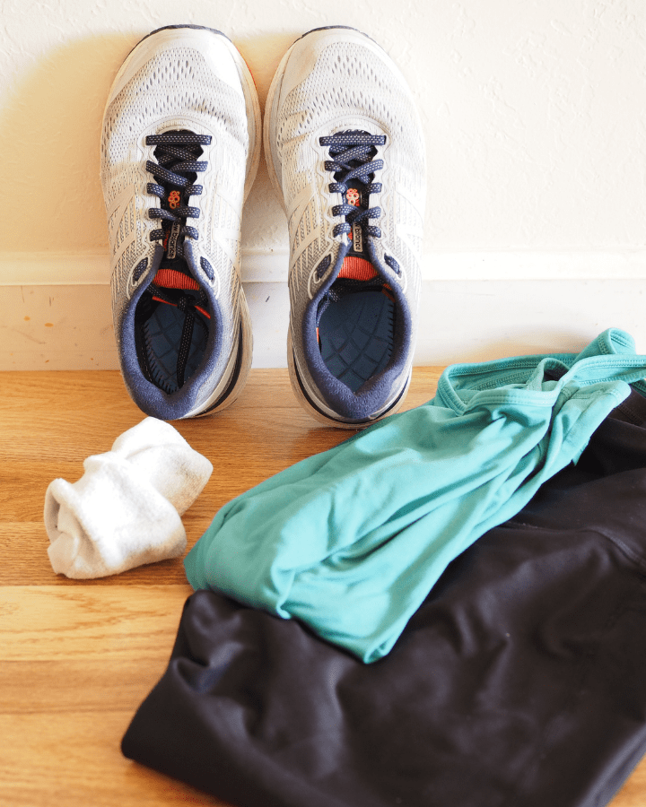 pair of workout shoes, socks, black workout pants, and blue shirt
