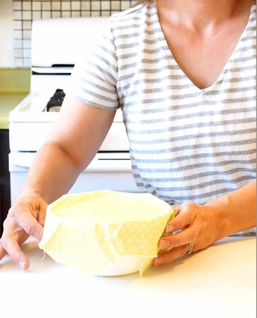 women placing a yellow beeswax wrap on a white bowl