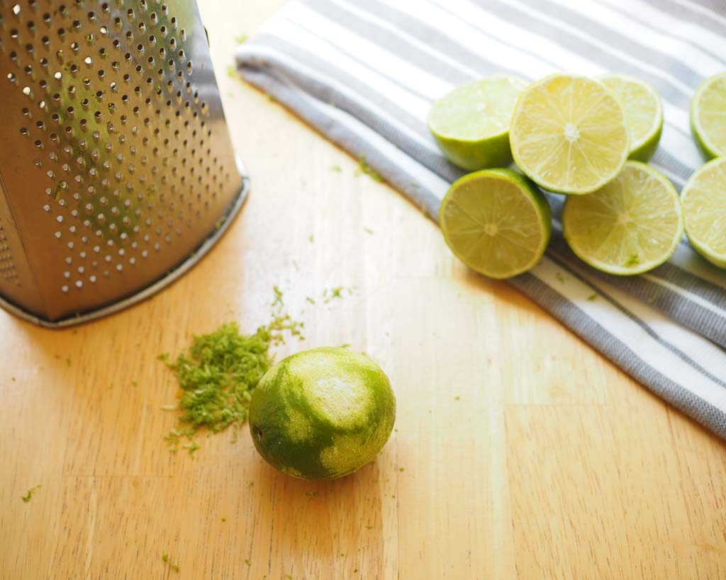 a zested green lime with a pile of limes