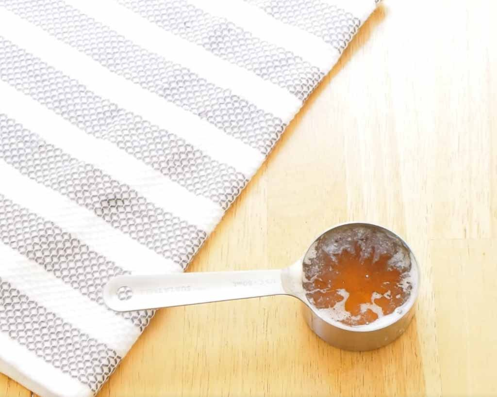 metal measuring cup with honey in it