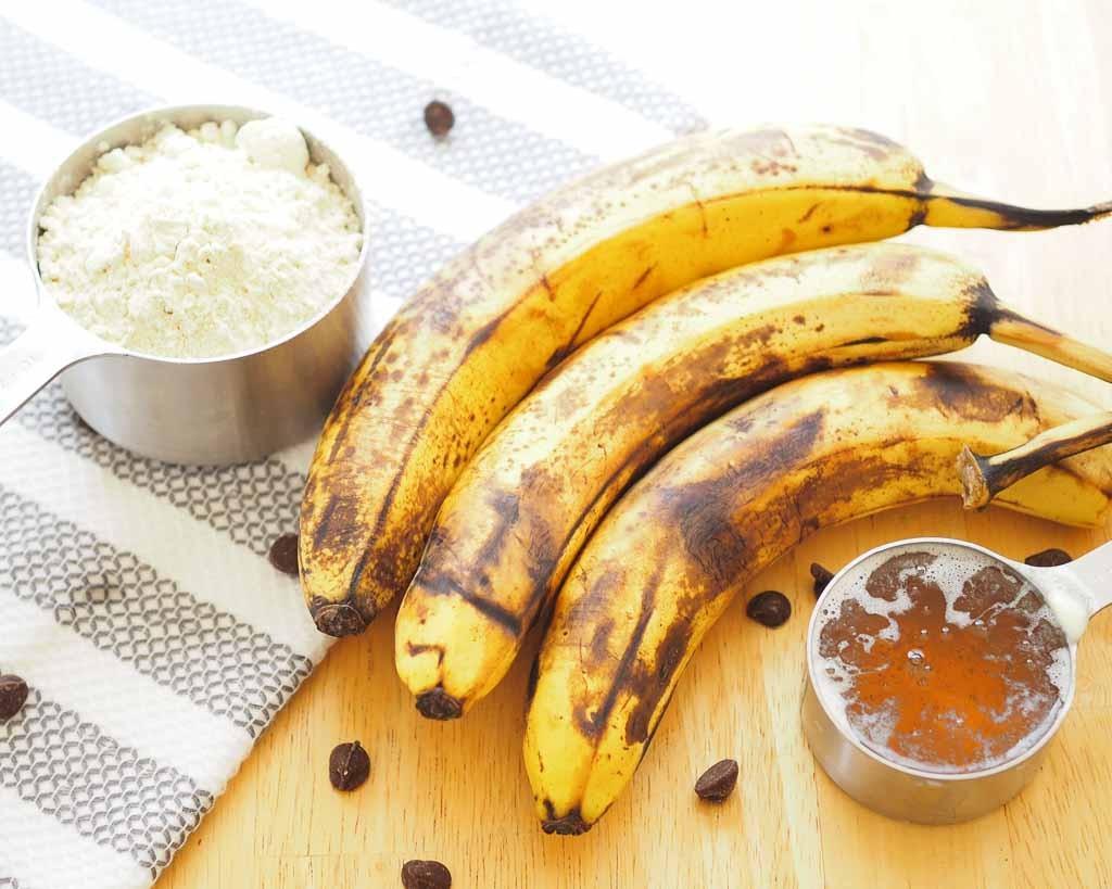 measuring cup of einkorn flour, honey, and three overripe bananas