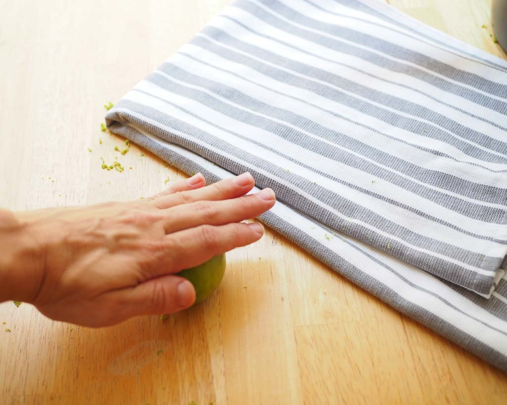 a hand rolling a green lime